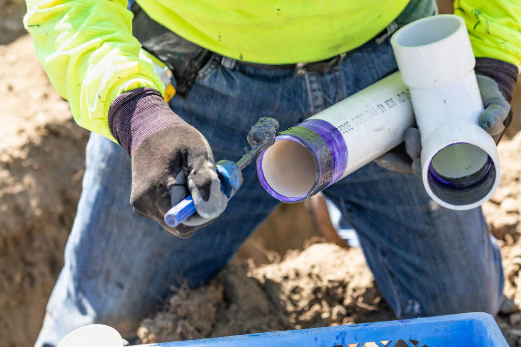 This Is A Picture Of A Plumber Putting Glue On PVC Pipe To Connect Two Pipes And Couples By Erie Pa Plumbers