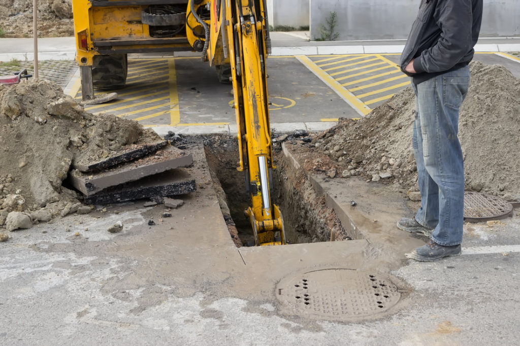 This Is A Picture Of A Machine Digging Up The Ground To Replace Some Plumbing Pipes In Erie PA