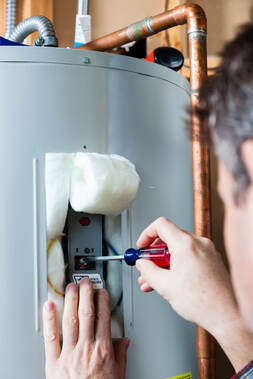 A picture of a man adjusting a hot water heater in Erie Pa