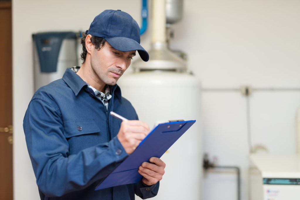 This Is A Picture Of A Erie Pa Plumber Taking Notes And Preparing A Plan For Replacement And Maintenance Erie Pa Plumbers
